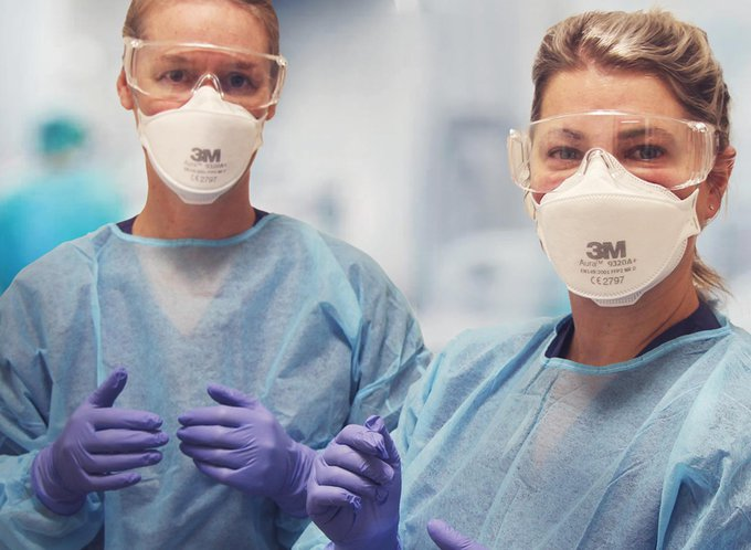 Personal protective equipment researchers Yvonne Anderson and Hailey Wells assist each other in putting on PPE